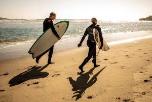 two people in wet suits carrying surf boards